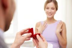 Jeune femme enthousiaste et ami donnant son anneau Photographie stock libre de droits