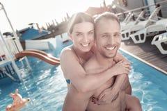 Jeune femme enthousiaste et homme embrassant dans la piscine Image stock
