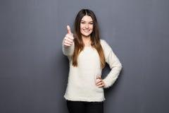 Jeune femme enthousiaste heureuse renonçant à des pouces Photographie stock