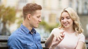 Jeune femme enthousiaste montrant la bague de fiançailles sur le doigt à l'ami aimé Photographie stock