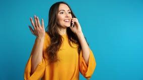 Jeune femme enthousiaste parlant par de bonnes nouvelles de téléphone et d'audition banque de vidéos