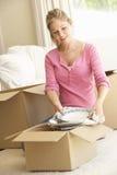 Jeune femme entrant dans la nouvelle maison déballant des boîtes Photo stock