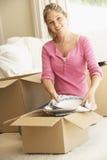 Jeune femme entrant dans la nouvelle maison déballant des boîtes Images stock