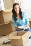 Jeune femme entrant dans la nouvelle maison déballant des boîtes Photos stock