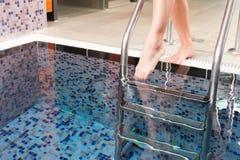 Jeune femme entrant dans le bassin de l'eau Photographie stock libre de droits