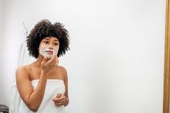 Jeune femme enveloppée en serviette blanche appliquant le masque naturel images stock