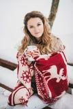 Jeune femme enveloppée dans la couverture buvant du thé chaud dans la forêt neigeuse Image libre de droits