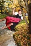 Jeune femme espiègle balançant sur un arbre Photos libres de droits