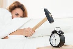 Jeune femme essayant de casser l'alarme avec le marteau image stock
