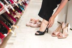 Jeune femme essayant sur des chaussures de talon haut tout en se reposant sur le sofa à s photographie stock