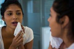 Jeune femme essuyant le visage image stock