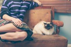 Jeune femme et chat sur le sofa Photos libres de droits