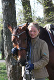 Jeune femme et cheval brun ensemble dans la forêt Image libre de droits