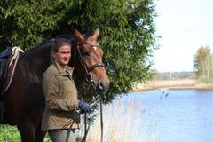 Jeune femme et cheval brun ensemble sur la côte de rivière Photos stock