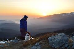 Jeune femme et chien au lever de soleil haut dans la montagne Image libre de droits