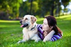 Jeune femme et chien d'arrêt d'or dans l'herbe Photographie stock