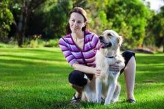 Jeune femme et chien d'arrêt d'or dans l'herbe Image libre de droits