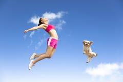 Jeune femme et chien sautant dans le ciel Photographie stock
