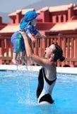 Jeune femme et descendant jouant dans la piscine Image stock