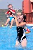 Jeune femme et descendant jouant dans la piscine Image libre de droits