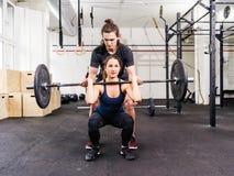 Jeune femme et entraîneur faisant des postures accroupies Photos libres de droits