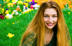 Jeune femme et fleurs à l'arrière-plan Photos stock