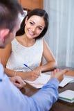 Jeune femme et homme avec les documents financiers à l'agence Images stock