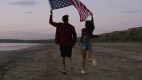 Jeune femme et homme courant sur le sable avec le drapeau américain augmenté, liberté se sentante Crépuscule de soirée cheminemen banque de vidéos