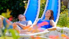 Jeune femme et homme dans des chaises de basculage banque de vidéos