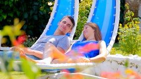 Jeune femme et homme dans des chaises de basculage clips vidéos
