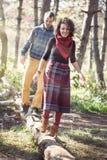 Jeune femme et homme dans des vêtements lumineux marchant le long du tronc tombé Images stock