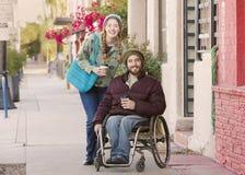 Jeune femme et homme dans le fauteuil roulant avec du café Images stock