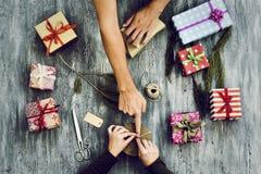 Jeune femme et homme enveloppant des cadeaux Photographie stock libre de droits