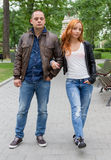 Jeune femme et homme marchant en parc de ville Photo stock