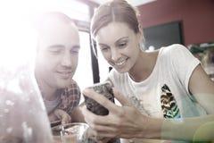 Jeune femme et homme partageant l'information sur le smartphone Photographie stock libre de droits