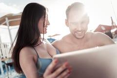 Jeune femme et homme regardant la tablette dehors photo stock