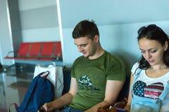 Jeune femme et homme s'asseyant dans une salle d'attente à l'aéroport Photographie stock