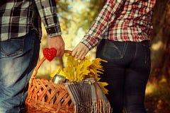 Jeune femme et homme tenant un panier avec la couverture, feuilles café, plan rapproché de jaune Photographie stock libre de droits