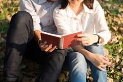 Jeune femme et jeune homme étreignant et tenant le carnet ensemble Images libres de droits