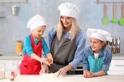 Jeune femme et sa cuisson de filles Images stock