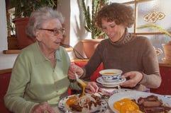 Jeune femme et sa grand-mère heureuse prenant le déjeuner au restaurant photos stock