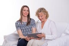 Jeune femme et sa mère avec le PC de comprimé Photo stock
