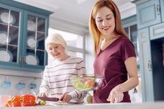 Jeune femme et sa mère faisant la salade ensemble Photos stock