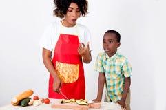 Jeune femme et son enfant préparant un repas avec l'avocat Photos stock
