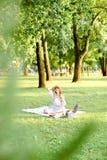 Jeune femme européenne dans le chapeau se reposant sur le plaid avec des fruits en parc photos libres de droits