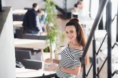 Jeune femme européenne magnifique avec la jolie tasse de boissons de visage de café tout en se tenant en café confortable Beau rê image libre de droits