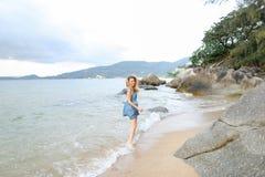 Jeune femme européenne marchant nu-pieds sur le sable, bord de mer de matin photo stock