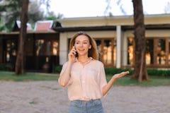 Jeune femme européenne parlant par smarptone près de la maison de station de vacances, du chemisier de port et des shorts photos stock