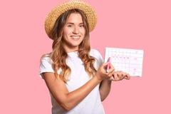 Jeune femme européenne positive dans le chapeau de paille, T-shirt blanc occasionnel, marqueur d'utilisations pour démontrer la p photo stock