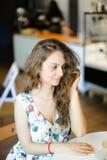 Jeune femme européenne s'asseyant au café et aux cheveux bouclés émouvants images stock